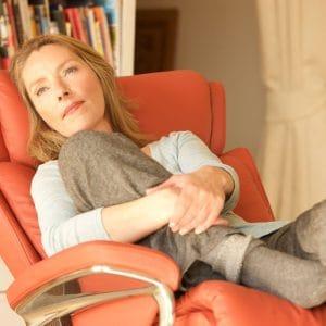 Stressless Sessel Magic Classic mit Lederbezug Paloma henna und Signature Untergestell braun mit Hocker Frau Nahaufnahme