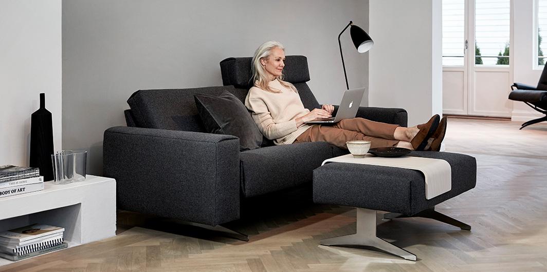 Frau auf Stressless Sofa mit Laptop, graues Sofa mit Fußbank